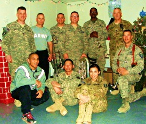 Peter (standing, closest to the Christmas tree) in Afghanistan with other soldiers.